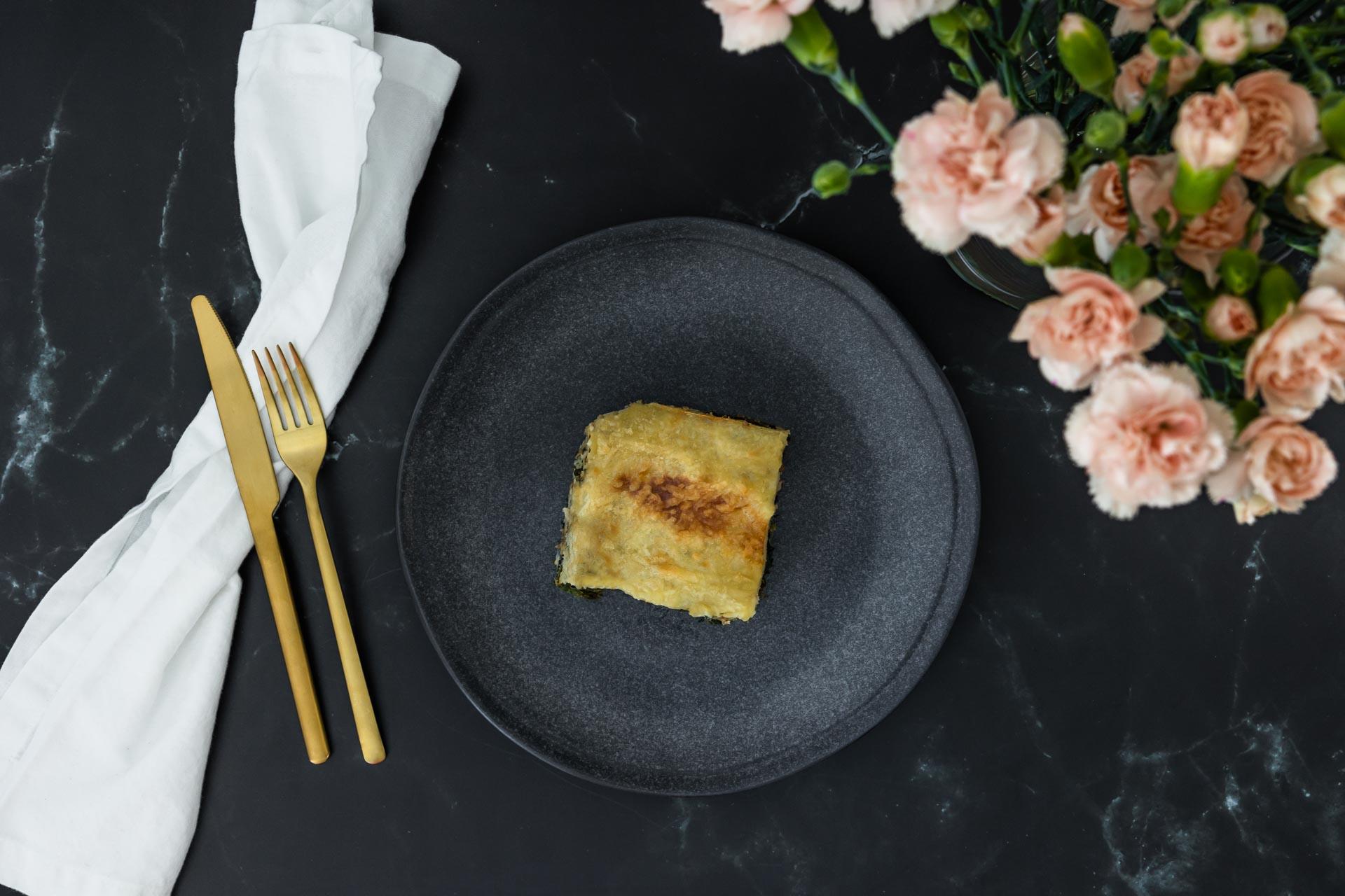 Spinat Lasagne vegan von oben mit Blumen und goldenem Besteck und weisser Serviette