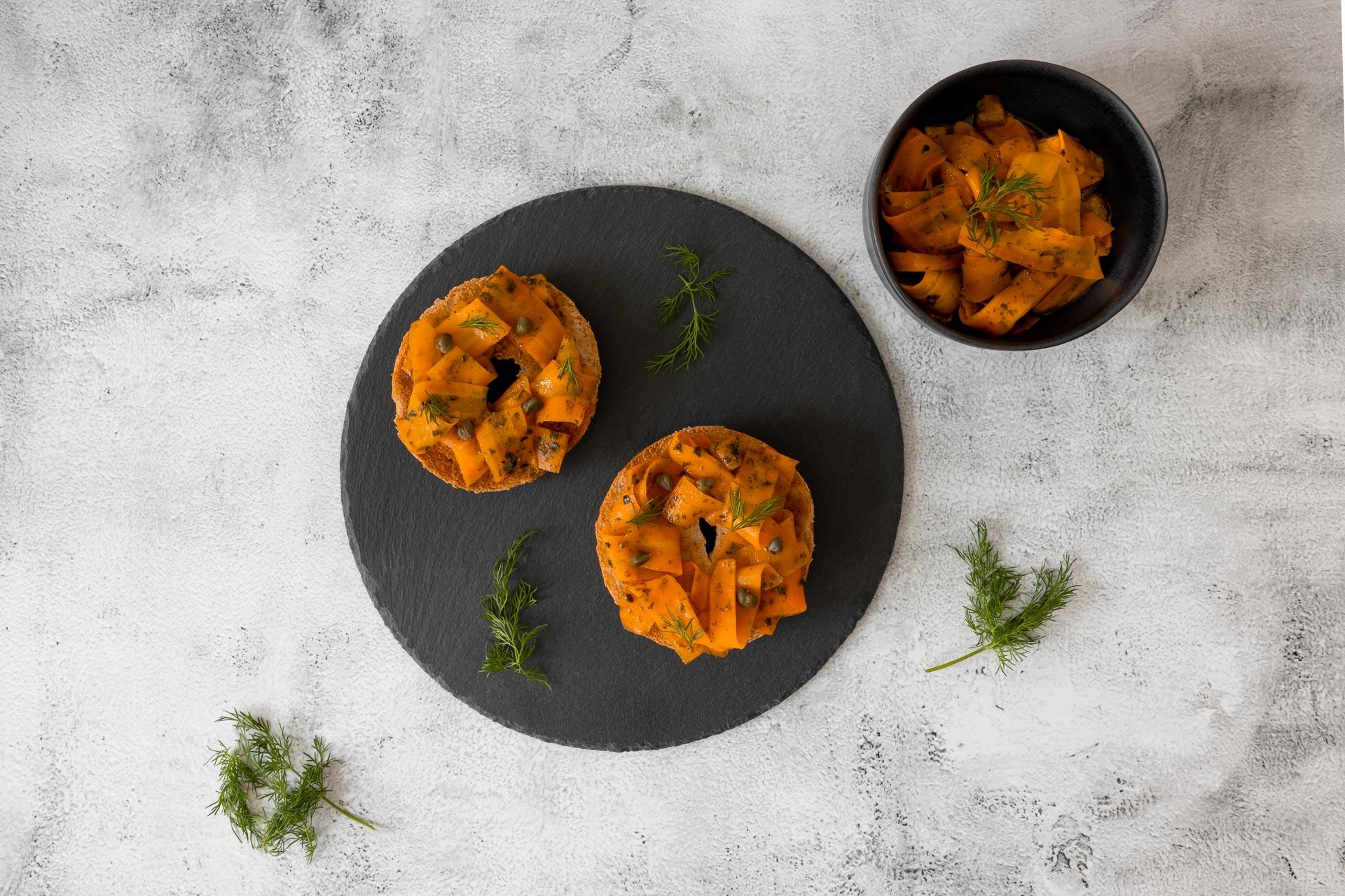 Veganer Lachs auf Beagel von oben mit Schale voll Karotten Lachs